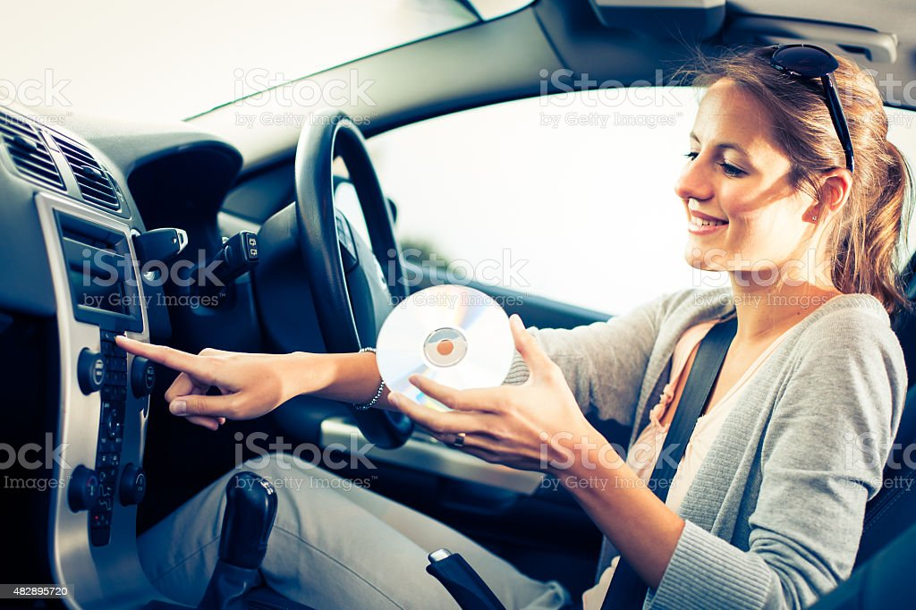 Young female driver playing music in the car stock photo