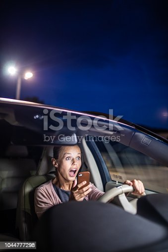 istock Young female driver playing with her cellphone instead of paying attention to driving startled in a potentially dangerous situation 1044777298