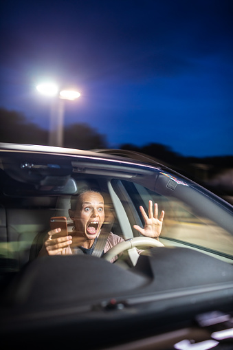 istock Young female driver playing with her cellphone instead of paying attention to driving startled in a potentially dangerous situation 1044781672