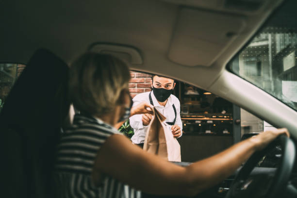 Young female driver recieving a packed food from a restaurant stock photo