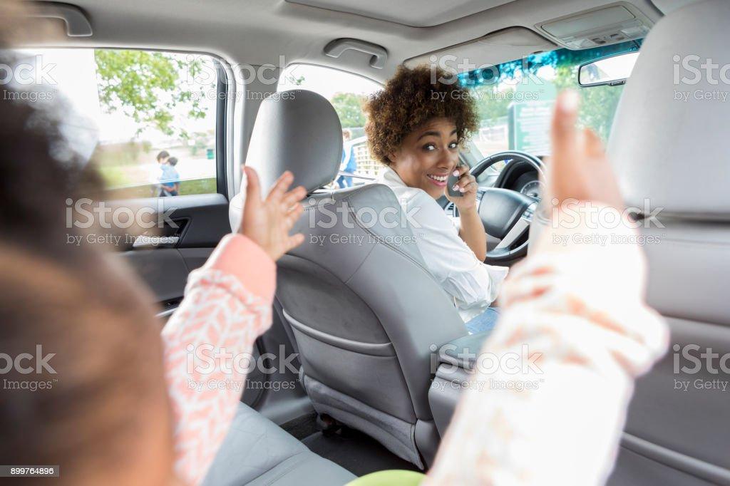 Junge Fahrerin lächelt Kind auf Rücksitz – Foto