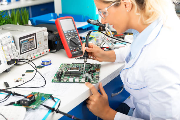 Young female electronic engineer soldering computer motherboard in laboratory Young attractive female digital electronic engineer repairing and soldering computer PC motherboard in laboratory soldering iron stock pictures, royalty-free photos & images