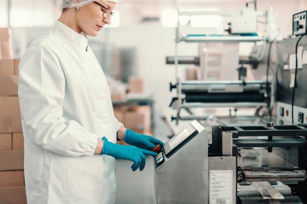 junge mitarbeiterin in sterilen uniform und blauen gummihandschuhen schaltet verpackungsmaschine ein, während sie in der lebensmittelfabrik steht. - grundnahrungsmittel stock-fotos und bilder