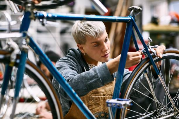 Junge Mitarbeiterin repariert Fahrradbremse – Foto