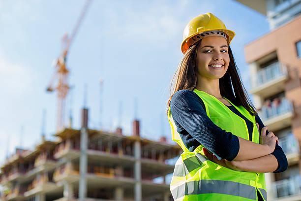 young female engineer smiling at construction site - arquitecta fotografías e imágenes de stock