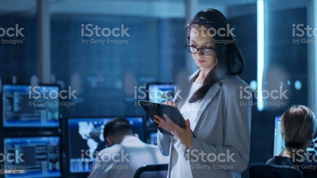 Joven ingeniera aplicaciones Tablet en centro de Control de sistema. En el fondo sus compañeros de trabajo están en sus espacios de trabajo con muchas pantallas mostrando datos valiosos. foto de stock libre de derechos