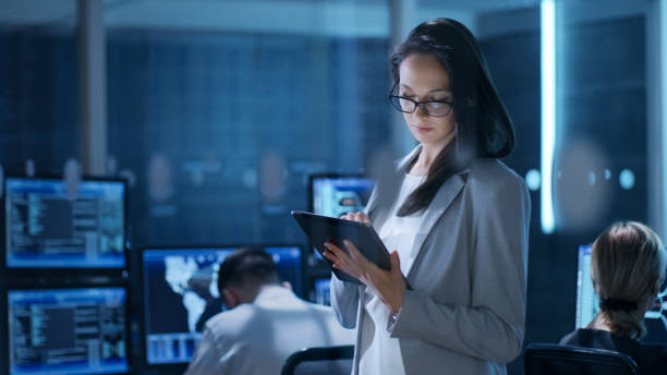 young female engineer uses tablet in system control center. in the background her coworkers are at their workspaces with many displays showing valuable data. - female spy stock photos and pictures