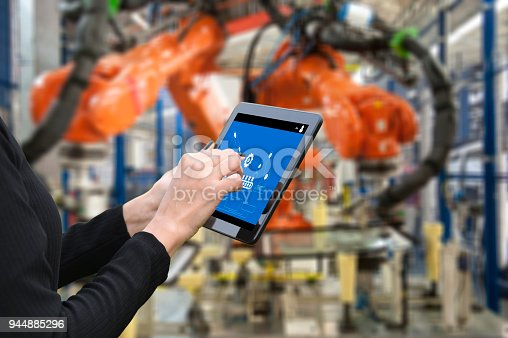 667596352istockphoto Young female engineer using digital tablet  to operate Robotic Arm 944885296