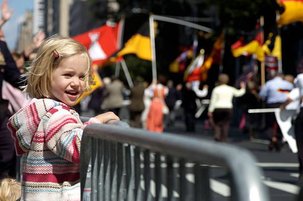 a young female enjoying a parade - geçit töreni stok fotoğraflar ve resimler