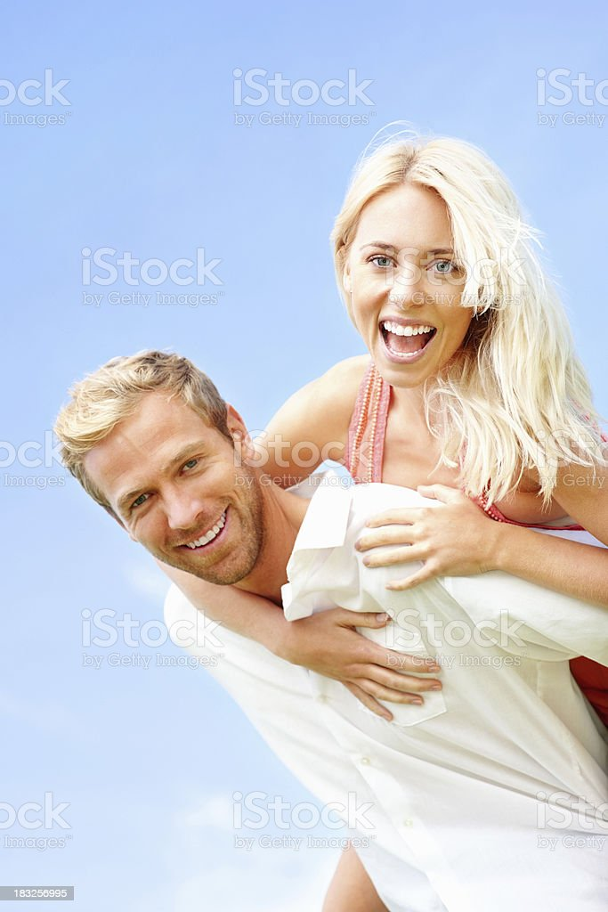 Young female enjoying a piggyback ride on boyfriends back royalty-free stock photo