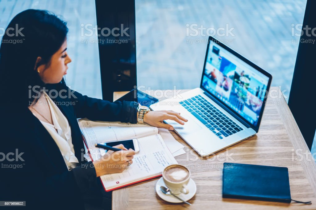 Young female entrepreneur dressed in trendy clothing searching information on laptop computer with mock up screen.Talented student preparing presentation for coursework project using modern device stock photo