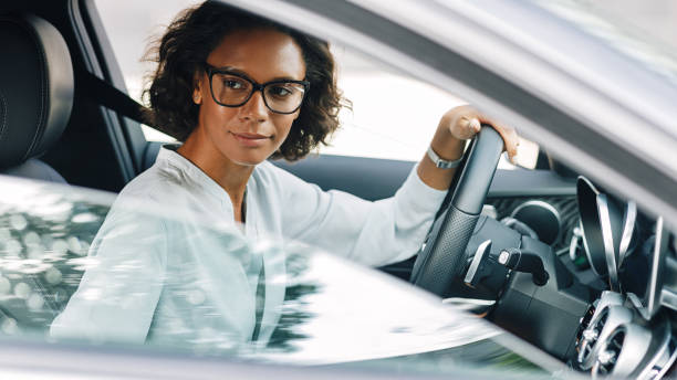 Young female entrepreneur driving a car looking away stock photo