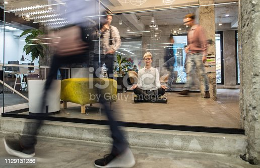 Young businesswoman exercising Yoga in Lotus position on the floor at casual office while their colleagues are walking in blurred motion. The view is through the glass.