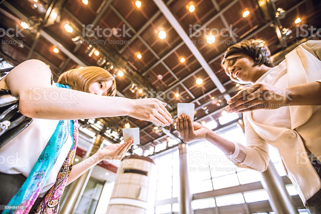 Young Female Entrepreneurs Exchanging Business Cards stock photo