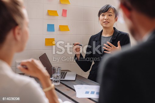 812513444istockphoto Young female executive giving presentation to colleagues 614028206