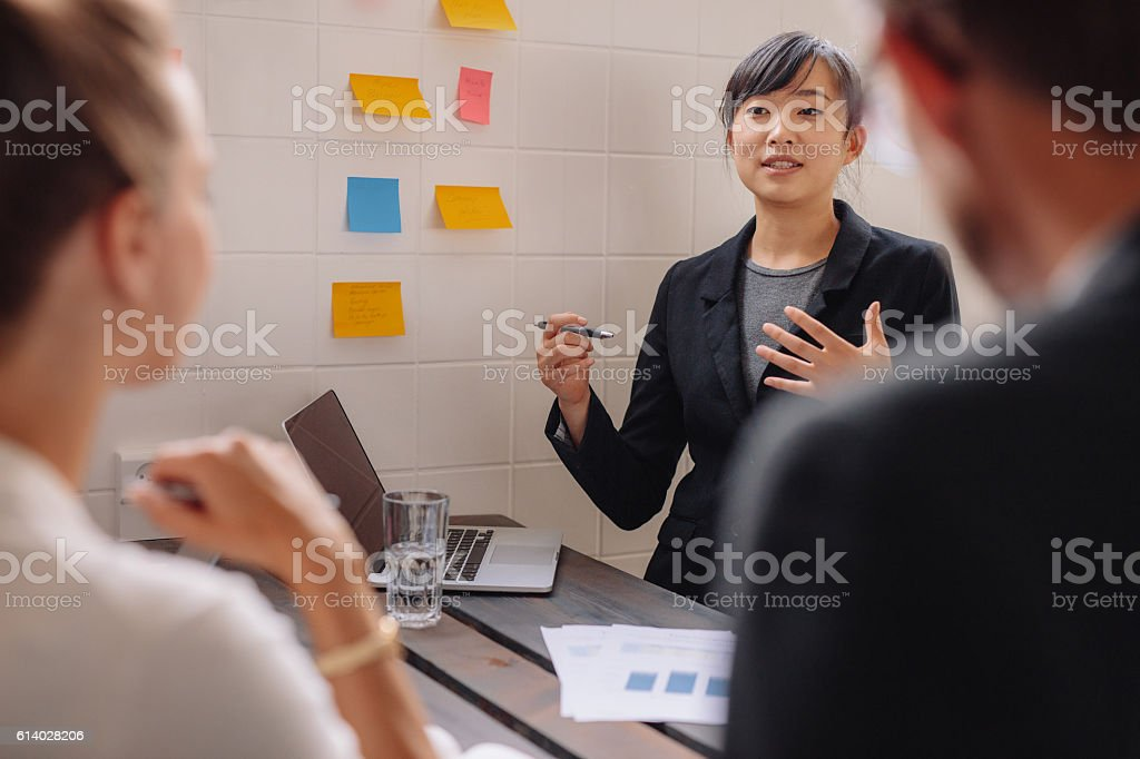 Young female executive giving presentation to colleagues stock photo