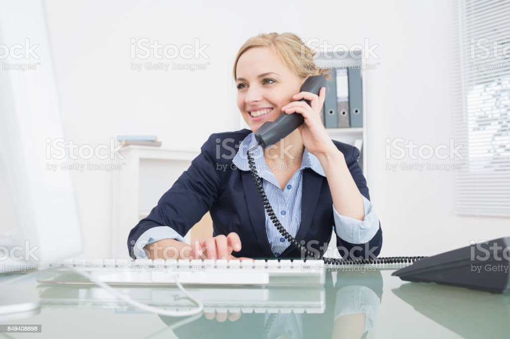 Young female executive using phone at office stock photo