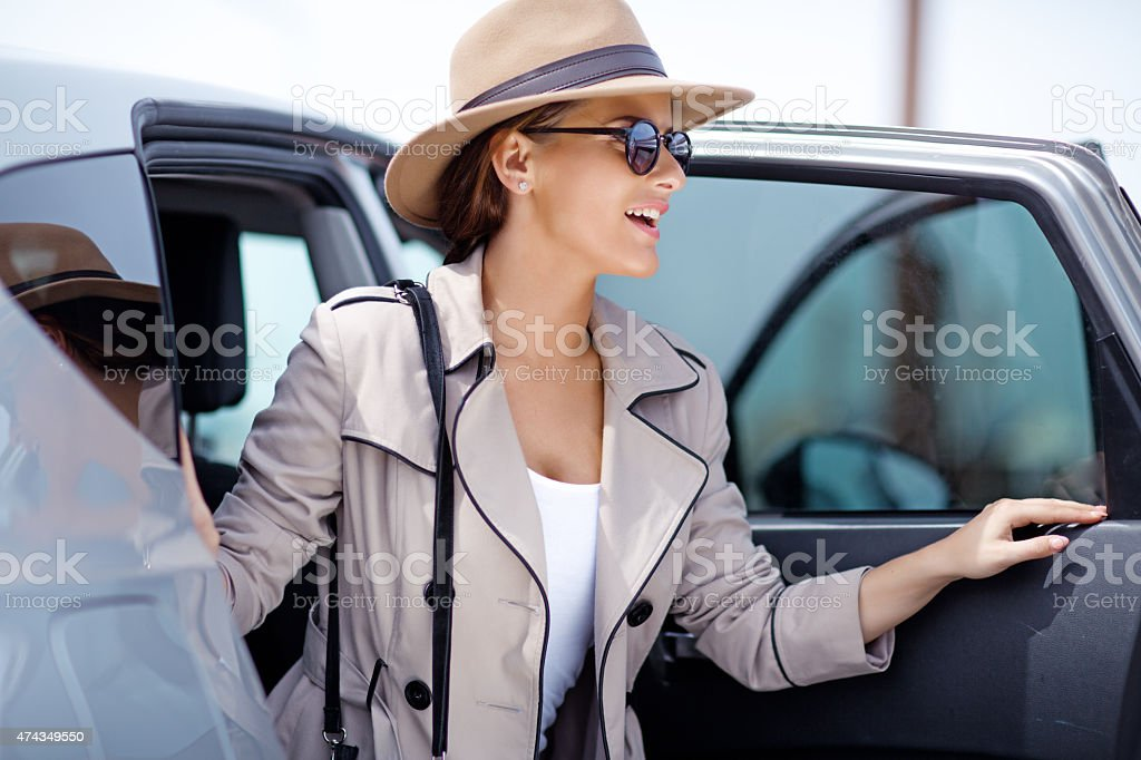 Young female exiting a car stock photo