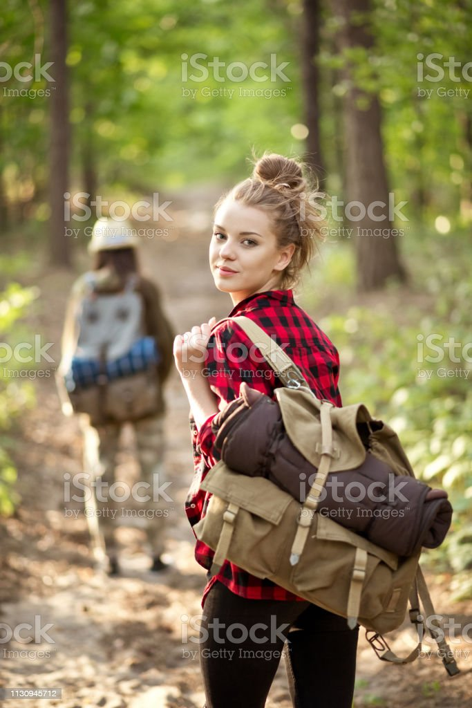 Young female explorer hiking with friend in forest Portrait of beautiful female explorer holding backpack. Young woman is hiking with friend in forest. They are exploring together during summer vacation. 20-24 Years Stock Photo