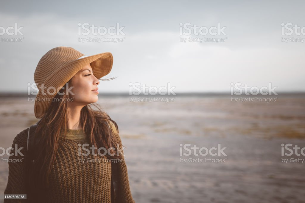 Young female explorer looking away in desert Thoughtful young woman looking away while standing against sky. Beautiful explorer is hiking in desert. Female hipster is wearing hat. 25-29 Years Stock Photo