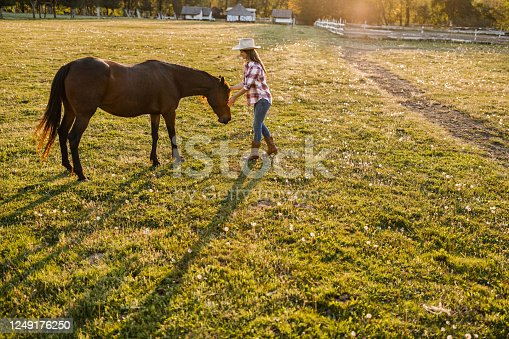 Young cowgirl spending a spring day with her horse on a farm. Copy space.