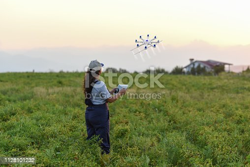 Young female farmer spraying her crops using a drone