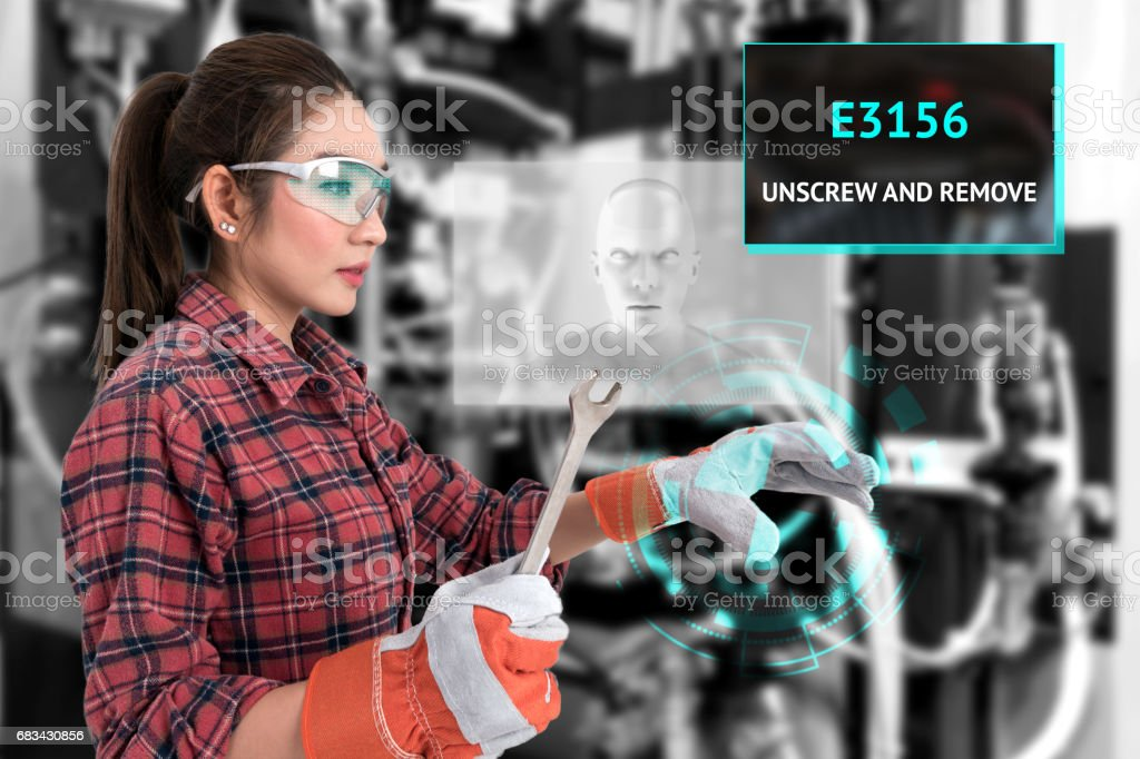 Young female farmer use Ar glasses artificial intelligence adviser to fix industrial machine and holding open end wrench with graphic. Augmented reality glasses technology , industry 4.0 concept. stock photo
