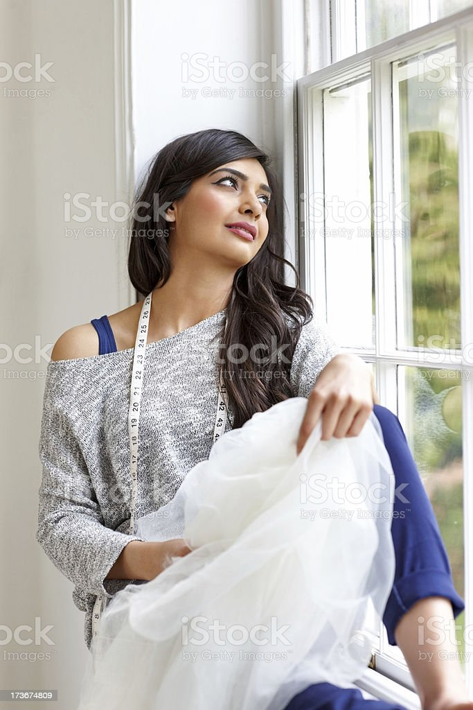 Young female fashion designer sitting by a window daydreaming royalty-free stock photo