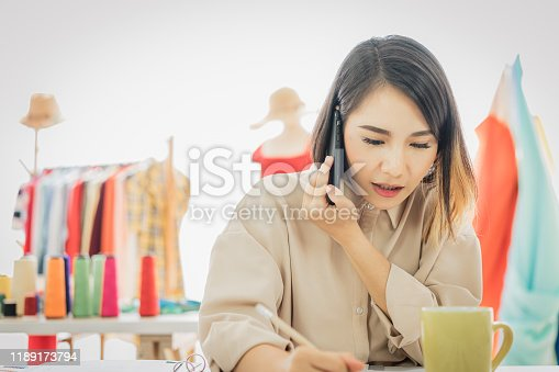 836871418 istock photo Young female fashion designer working and talking on mobile phone with customer in front of laptop computer on her designs in the studio. 1189173794