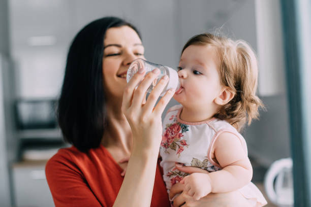Young female feeds baby daughter in kitchen at home stock photo