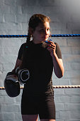 Young female fighter about to put her mouth guards in while holding her boxing glove with her other hand. She is standing in the ring, part of her is in shadow.