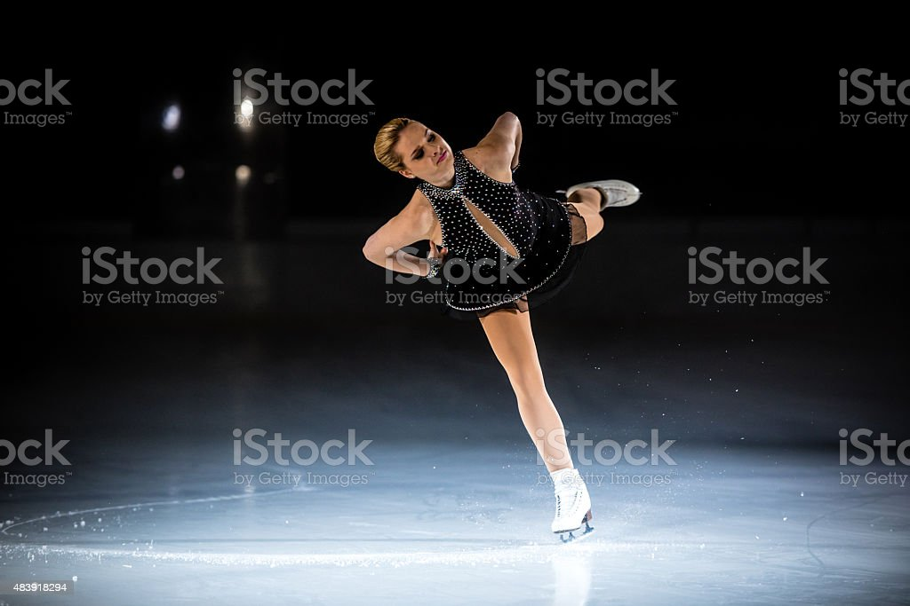 Young female figure skater performing stock photo