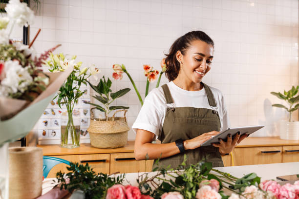 Young female florist making notes on a digital tablet. Woman checking online orders in shop. stock photo