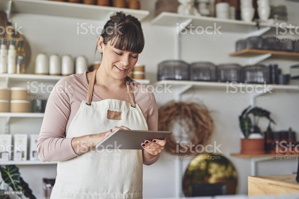 Joven mujer Florista utilizando una tableta digital en su tienda de flores - foto de stock