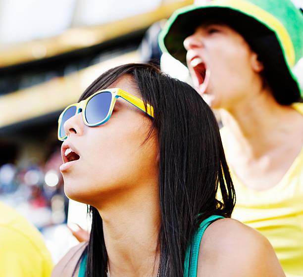 junge weibliche fußball-fans sind uneingeschränkt beteiligt bei einem spiel - spielerfrauen stock-fotos und bilder