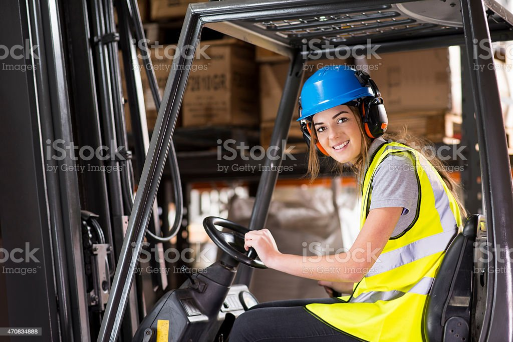 young female forklift driver in a warehouse stock photo