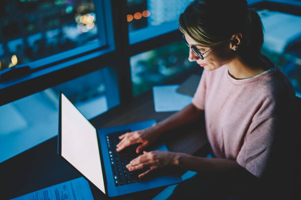 Young female freelancer owner keyboarding information about new implementation in startup project using laptop with mock up screen working late at night. Woman working overtime on computer in office stock photo