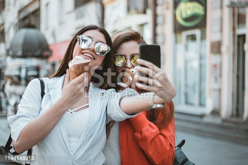 Two Beautiful and Attractive Women with Long Hair and Sunglasses are Photographing Themselves in the Street. They are Smiling While Eating Cold Ice Cream on a Beautiful Spring Day.