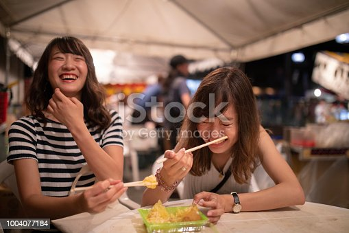 Young female friends enjoying in night festival
