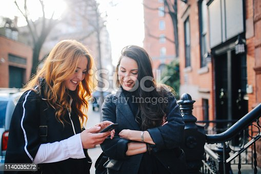 Female friends walking in the Lower Manhattan, New York, having a nice and relaxed day together, enjoying the springtime. They're wearing fashionable, casual clothes, talking, spending time together.