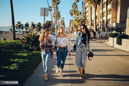 Vintage toned, warm colored image of young female friends, walking on the Venice beach boardwalk in Los Angeles, California. They're having a nice time, spending the afternoon together.
