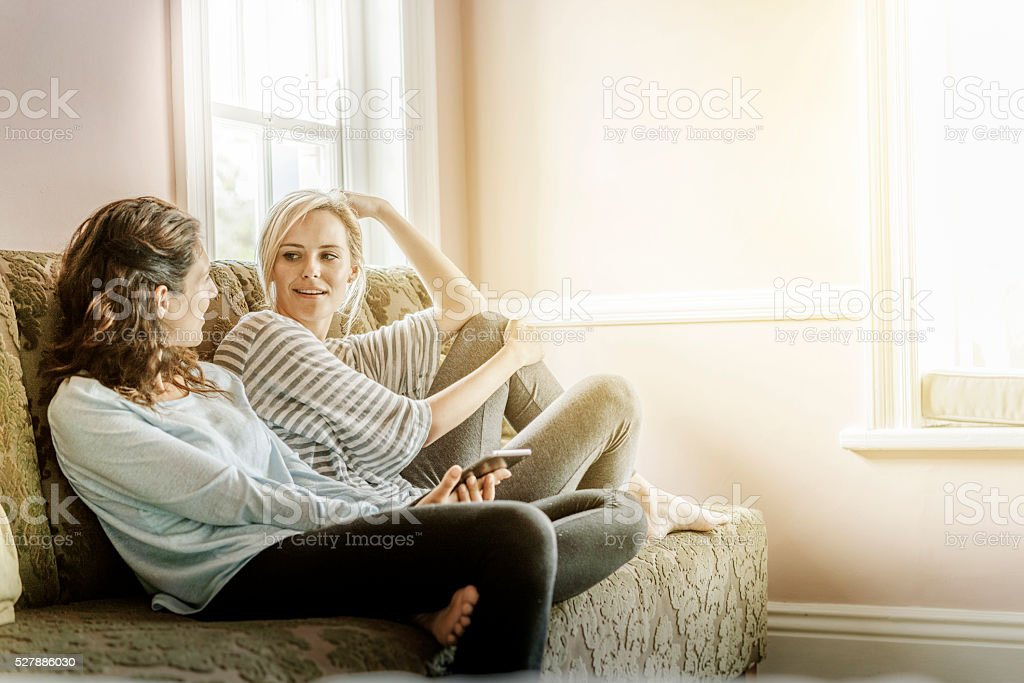 Young female friends gossiping on sofa at home stock photo