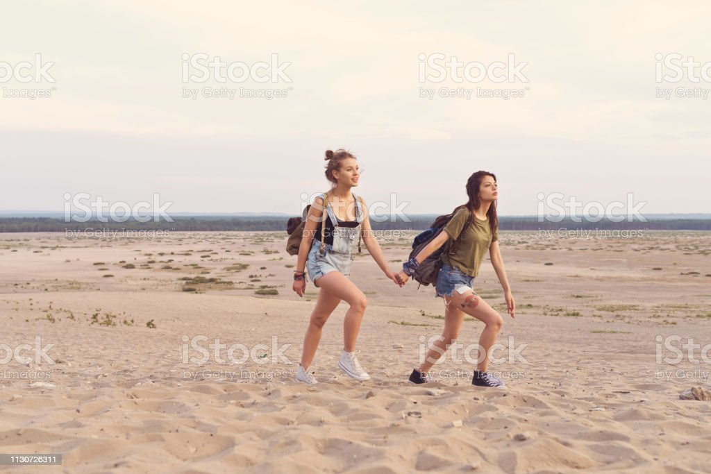 Young female friends hiking in desert Young women holding hands while walking on sand. Female friends are hiking in desert. They are spending vacation together. 20-24 Years Stock Photo