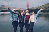 Five, young, female friends gathering in front of the Golden Gate Bridge for a picture.
