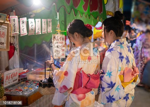 Young female friends in yukata shopping at Japanese Yatai market in festival