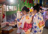 浴衣祭りで屋台の日本市場での買い物で若い女性の友人