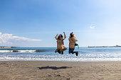 ビーチでジャンプ若い女性の友人