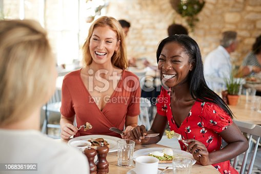 Young female friends smiling at brunch in a cafe, close up