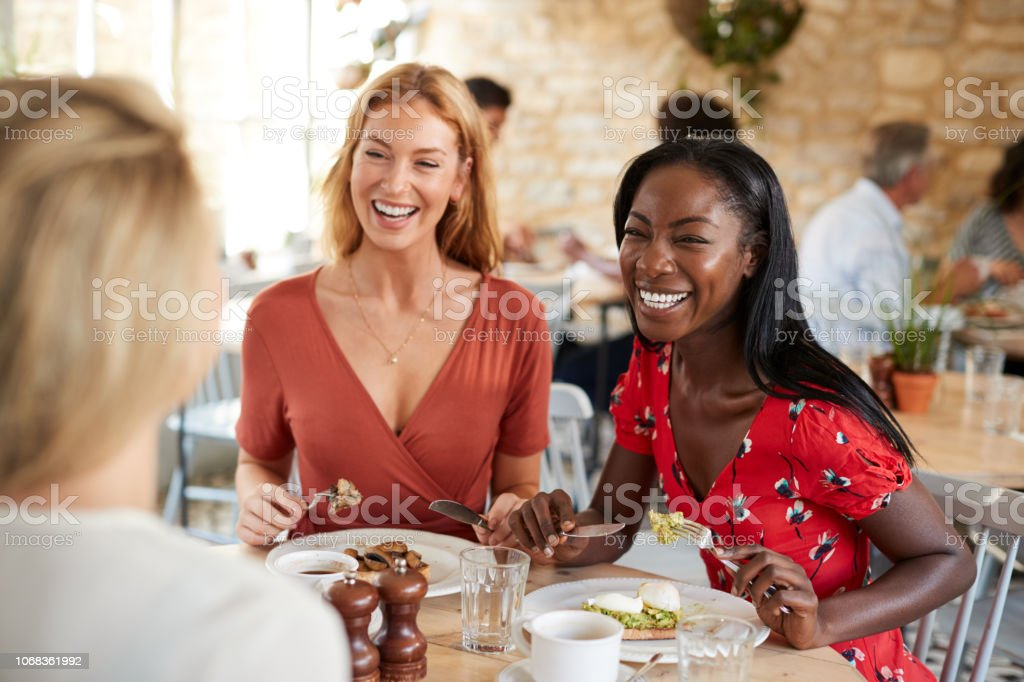 Young female friends smiling at brunch in a cafe, close up stock photo