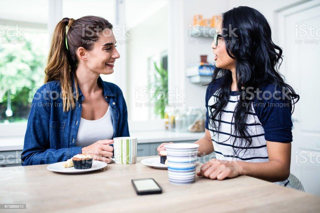 Kahvaltı yaparken konuşan genç kadın arkadaşlar royalty-free stock photo